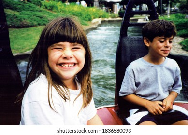 Young siblings on a water ride, happy and smiling at the amusement park.  Vintage scan of 1990s family photo (1997).