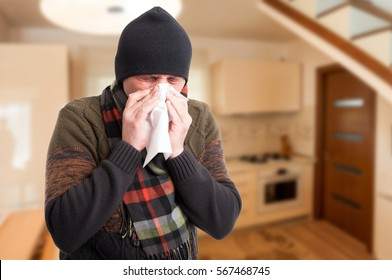 Young sick man holding tissue and blowing nose inside the house with copy text space