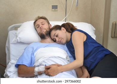 young sick man lying in bed at hospital room after suffering accident having his worried and caring wife or girlfriend together holding his hand giving him love and support