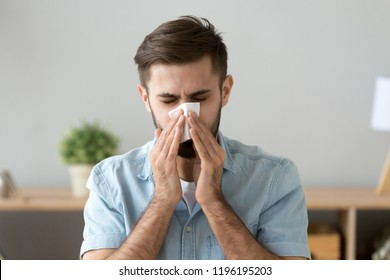 Young sick man sitting at office room sneeze holding tissue handkerchief blowing wiping his running nose. Headshot Male feels unwell caught influenza cold seasonal infection or having allergy concept