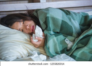 young sick sweet Asian American girl in pajamas covered with blanket lying feverish on bed suffering cold and flu in medical health care and influenza virus disease concept