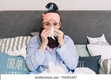 Young sick woman in bed with flu and cold blowing her nose