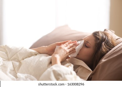 Young sick woman blowing her nose while in bed