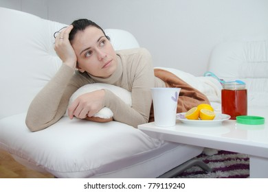 Young sick woman laying in bed