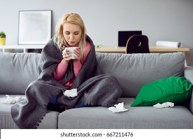 Young sick woman sitting on sofa drinking tea