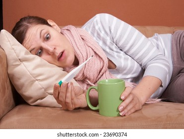 A young sick woman with a thermometer in her mouth and with a cup of tea in her hand. She is stunned by her high temperature.