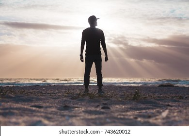 young silhouette man standing on beach