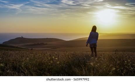 Young silhouette woman stands in a field looking into the sunset and distance