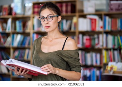 Young simpatic woman wearing fashionable colorful glasses and one shoulder cotton blouse holding a book in hands while looking to camera on a bookshelf background, in a library.