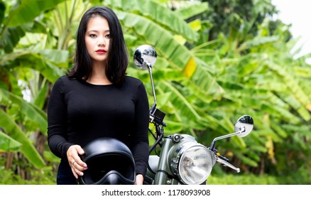 Young  Singaporean woman holding an helmet. Behind her, a green motorcycle and a tropical background