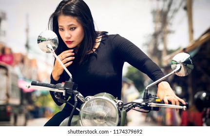 Young  Singaporean woman on a green motorcycle, checking her make up on the rearview mirror. Behind her, a street market
