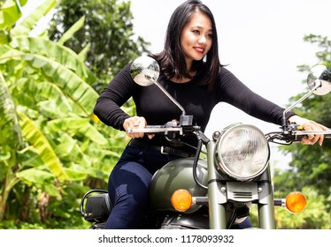 Young  Singaporean woman on a green motorcycle.  Behind her, a tropical background