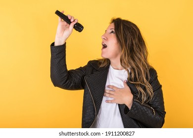 Young singer girl wearing black leather jacket singing with microphone on yellow background.