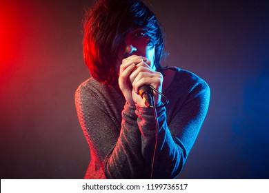 The young singer or vocalist in emo style is singing on concert on background of red and blue concert lights.