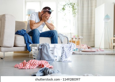 Young single father overwhelmed with household chores sitting on sofa in messy living room.