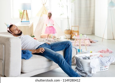 Young single father overwhelmed with household chores sleeping on sofa in messy living room with his little daughter playing in the background.