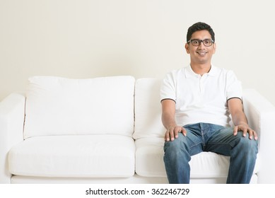 Young single Indian guy sitting lonely on sofa and smiling. Lifestyle Asian man at home. Handsome male model.