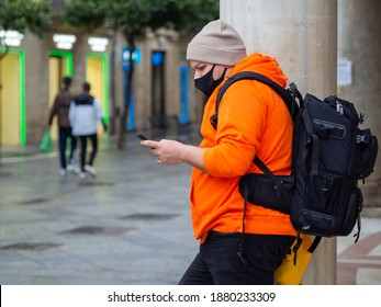 A young single male in a facial mask and orange hoodie leaning on a wall and checking his phone - new normal concept