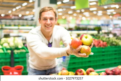 Young single man showing fruit and vegetables at shopping in grocery store supermarket - Modern healthy lifestyle concept with guy on bio food products purchase at vegetarian market place