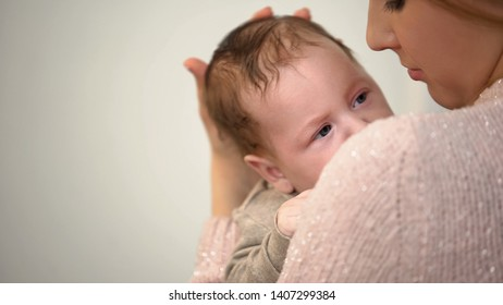 Young single mother holding newborn baby tenderly, governmental aid, support