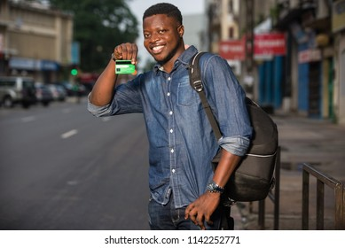 Young single traveler on the street at the platform of the station with backpack. Smiling man showing credit card, waiting for vehicle at train station for trip.