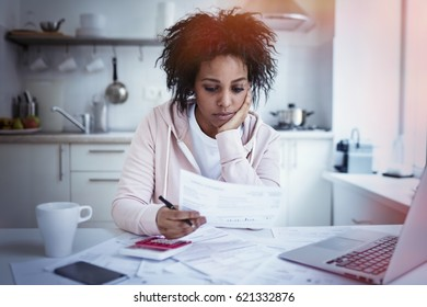 Young single upset african american housewife sitting at kitchen table with papers, laptop and calculator, trying to make both ends meet, having no money to pay debts. Financial problems concept