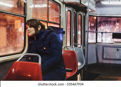 Young single woman in blue jacket sitting in an empty tram. On the street the evening and rain.