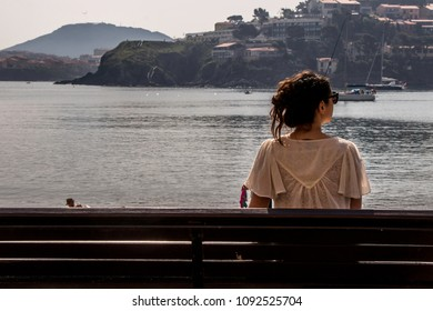 young single woman sitting on a bench facing the sea, Collioure in East Pyrenes, France