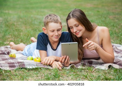 Young sister and brother with freckles on their faces lying down on plaid and using tablet in park. she is showing display with her finger and smiling.