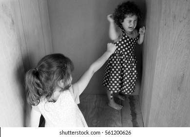 Young sister girls (age 7 and 3) fighting at home. Children childhood concept. Real people copy space (BW)
