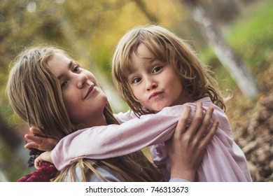 Young sisters hugging happy in their backyard.