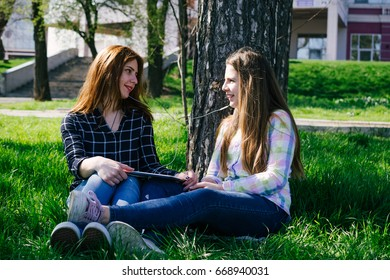 Young sisters relaxing listening to music with tablet together in the park