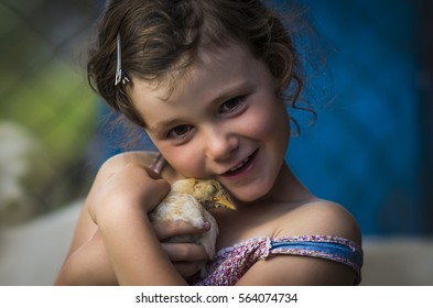 Young six year old girl cradling chick in her arms.
