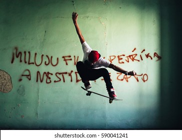 Young skateboarder caught in peak moment of his stunt with arms outstretched, board lightly touching shoes. In background wall of room in abandoned house with sprayed text. Natural light conditions.
