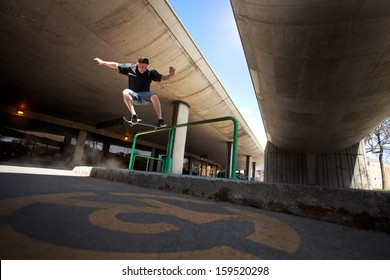 Young Skateboarder doing a Crooked Grind trick on a Rail