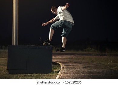 Young Skateboarder doing a Frontside Boardslide trick at Night