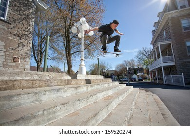 Young Skateboarder doing a Ollie down the stairs