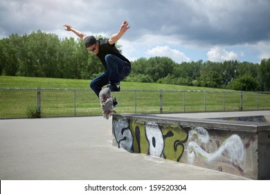 Young Skateboarder doing a Wallie in a skatepark