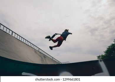 Young skateboarder ramp on extreme skatepark. Skater jumping on ramp at city park. Young man performing tricks and skills with skateboard. Recreation skateboarding concept.