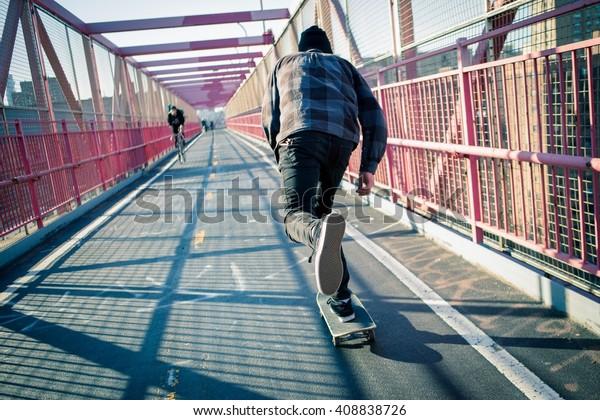 ニューヨーク市ウィリアムスバーグブリッジの歩道を、若いスケートボーダーのスピードで通り抜ける。2016年2月に撮影。