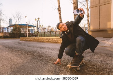 Young skateboarder taking a selfie at his skateboard on sunset day with copy space