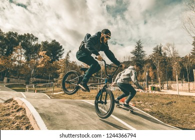 Young skateboarders and bmx bikes. Young people practicing sports in the city