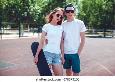 Young skater boy and girl with skateboard in white T-shirts on the basketball court.