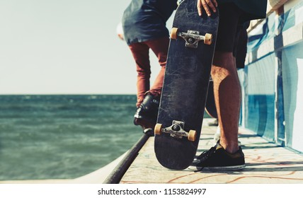 Young skater boy holding old used skateboard. Extreme summer sports festival on the beach. Skateboarder with wooden deck in hands posing on skate ramp outdoor