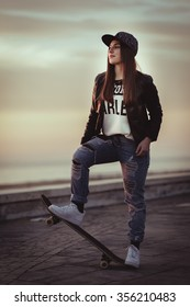Young skater girl watching sunset