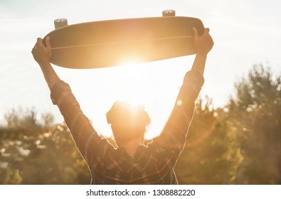 Young skater holding longboard outside with back sun light - Man from behind with skateboard in his hands at sunset - Freedom, success and extreme sport concept - Focus on head silhouette