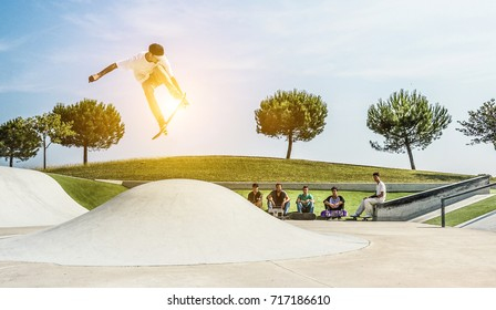Young skater jumping with skateboard in city skate park - Sporty guy performing tricks and skills  - Extreme sport concept - Soft focus on him - Warm contrast filter