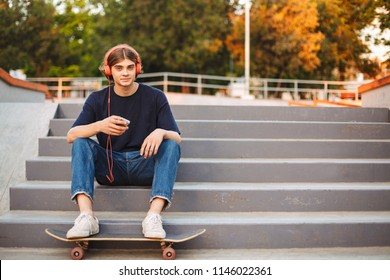 Young skater in orange headphones holding cellphone in hands happily looking in camera on stairs with skateboard at skate park