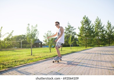 Young skater performing with longboard at sunset in city park. Trendy man having fun with skateboard outdoors, extreme fitness and sport concept