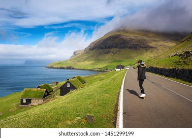 Young skater riding a skateboard through the coastal village of Bour on the Faroe Islands surrounded by beatiful scenery